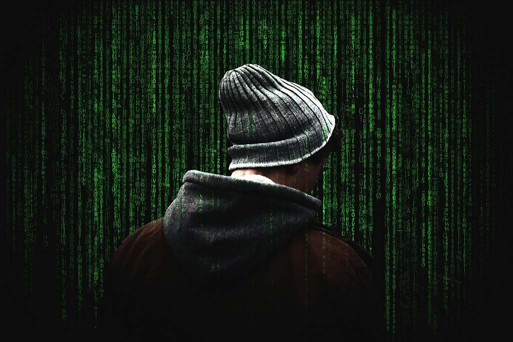 hacker in a hoodie with a digital backdrop