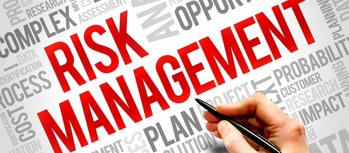 Risk Management in red type with hand and pen